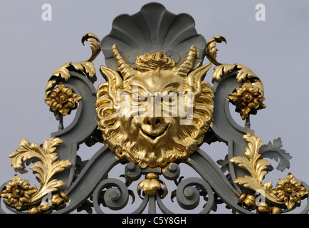 Decoration on the gates of Hampton Court Palace in the form of the face of a satyr. Hampton Court Palace, Surrey, - Stock Photo