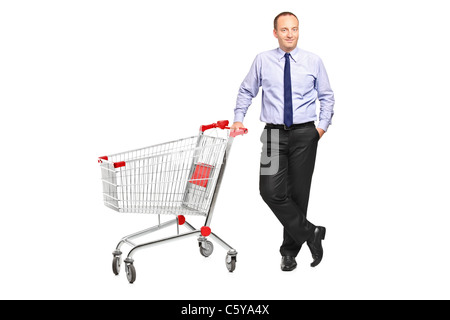 Full length portrait of a man posing next to an empty shopping cart - Stock Photo