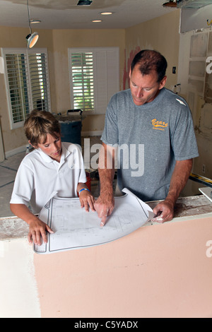 caucasian Father and 11-12 year years old son boy helping work experience together read blueprint pattern plans - Stock Photo