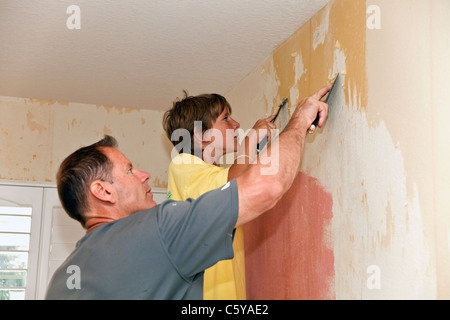 Caucasian Father and 11-12  year years old son helping working together to remove wallpaper from wall. MR © 2011 - Stock Photo