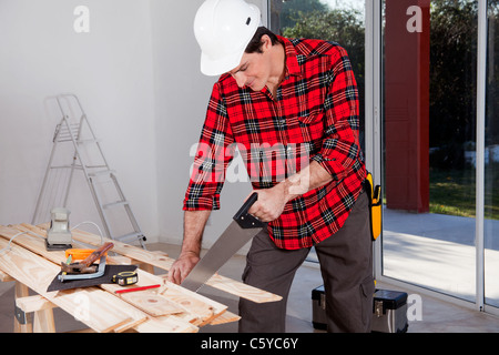 A construction worker using a hand wood saw while wearing a white safety helmet - Stock Photo