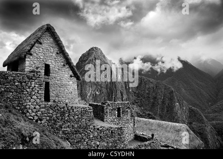 Scenic view of Machupicchu high up in the Peruvian Andes. With wooden hut and misty mountains. Monotone image. - Stock Photo
