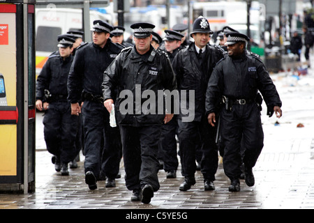 Police in public order gear changing over manning of cordons on tottenham High following a night of disorder and - Stock Photo