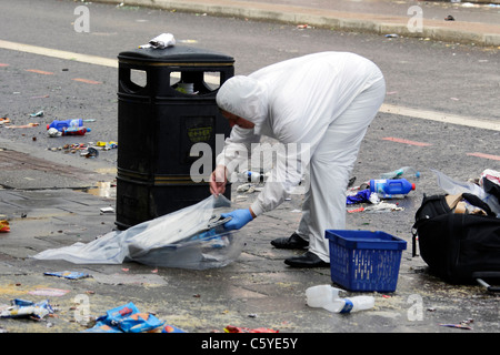 Finger tip search for evidence by crime scene investigators on Tottenham High Road following a night of rioting - Stock Photo