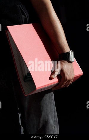 Male holding an A4 red ring binder folder in his left hand - Stock Photo