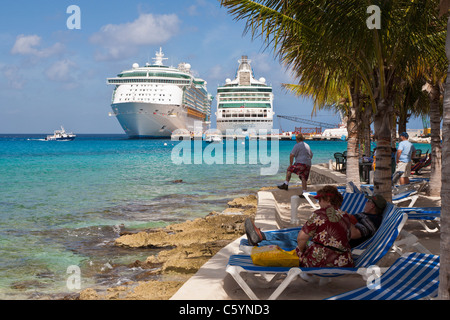 Tourists on beach watch cruise ship activity at the port of Cozumel, Mexico in the Caribbean Sea - Stock Photo