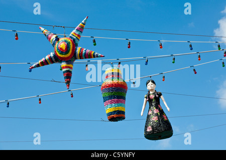 Pinatas hanging on strings of lights against blues sky in Cozumel, Mexico in the Caribbean Sea - Stock Photo