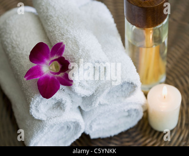 USA, California, Oakland, rolled up towels, aroma sticks, candle and orchid on table - Stock Photo