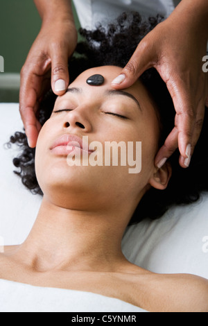 USA, California, Oakland, young woman receiving stone spa treatment - Stock Photo