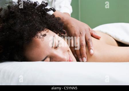 USA, California, Oakland, young woman having back massage - Stock Photo