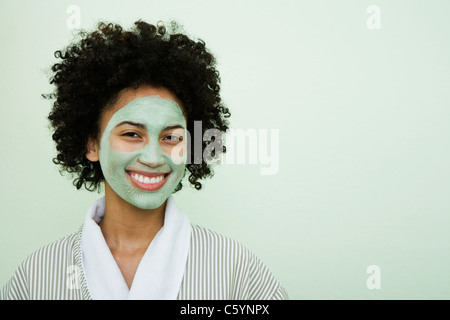 USA, California, Oakland, portrait of smiling young woman with facial mask - Stock Photo