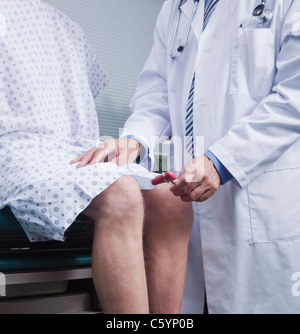 USA California, Larkspur, Doctor checking patient's reflexes with reflex hammer, mid section - Stock Photo