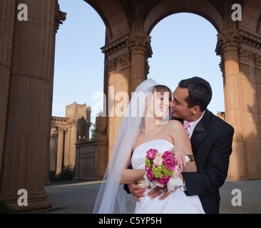 USA, California, San Francisco, bride and groom embracing under arches - Stock Photo