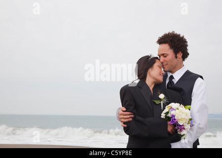 USA, California, San Francisco, Baker Beach, bride and groom on beach - Stock Photo
