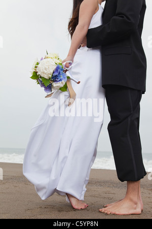 USA, California, San Francisco, Baker Beach, bride and groom walking on beach - Stock Photo