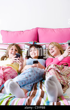 USA California, Fairfax, teenage girls (14-15, 16-17) lying on bed and looking at mobile phones - Stock Photo