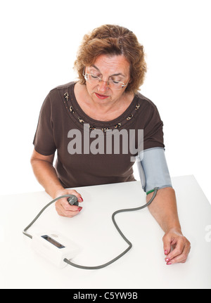 senior woman check her blodd pressure with machine - Stock Photo