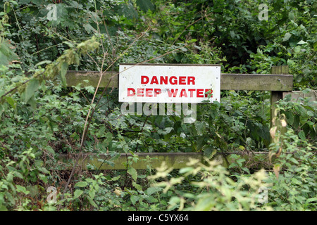 Danger of deep water warning sign in summer undergrowth on a path in Grovely Woods, Wilton, Wiltshire UK. - Stock Photo