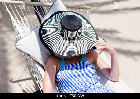 A woman covering her face with a floppy hat in a hammock in Antigua - Stock Photo