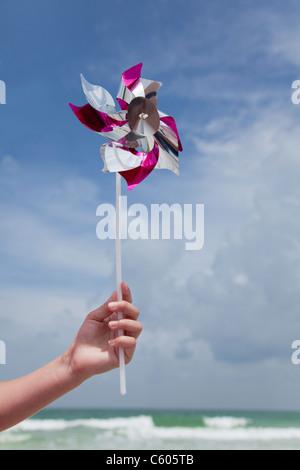 USA, Florida, St. Pete Beach, Girl's (8-9) hand holding pinwheel on beach - Stock Photo