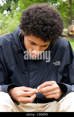 London Parliament Hill Hampstead Heath portrait of an angler or fisherman young man boy youth or male putting bait - Stock Photo