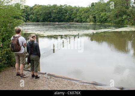 London Parliament Hill Hampstead Heath Highgate no. 1 pond young couple admire view knapsack shorts cut offs lake - Stock Photo