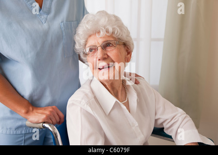 USA, Illinois, Metamora, Female nurse assisting senior woman on wheelchair - Stock Photo
