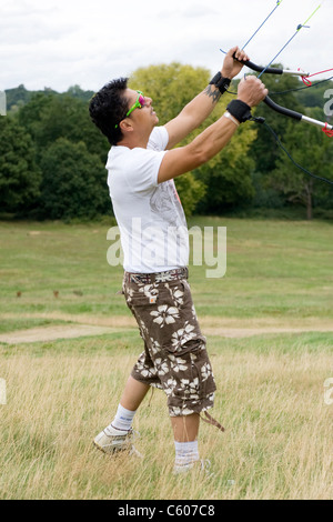 London Parliament Hill Hampstead Heath young Asian man in shorts & sunglasses flies new kite for first time hobby - Stock Photo