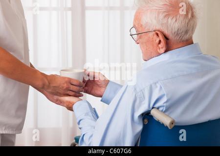 USA, Illinois, Metamora, Female nurse handing drink to senior man on wheelchair - Stock Photo