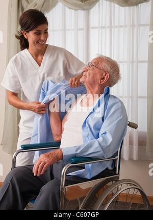 USA, Illinois, Metamora, Female nurse assisting senior man in dressing himself - Stock Photo