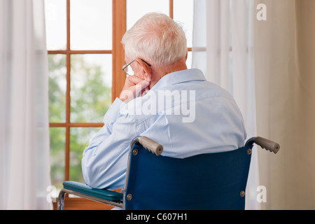USA, Illinois, Metamora, Rear view of senior man on wheelchair resting in front of window - Stock Photo
