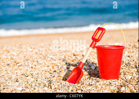Red Childrens Toy Bucket and Spade on the Beach - Stock Photo