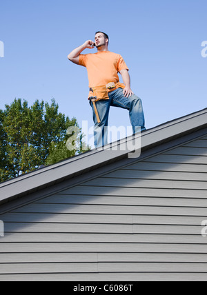 USA, Illinois, Metamora, Young worker standing on roof and talking via mobile phone - Stock Photo
