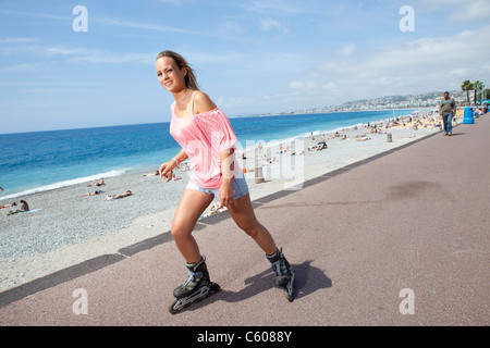 woman on rollerskates seafront beach Nice France - Stock Photo