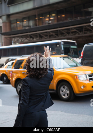 USA, New York, New York City, rear view of woman hailing taxi - Stock Photo