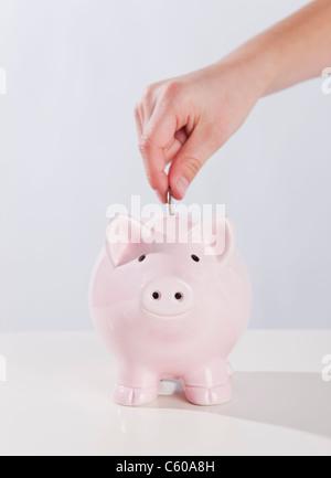 USA, Illinois, Metamora, Child's (10-11) hand putting money into piggy bank - Stock Photo