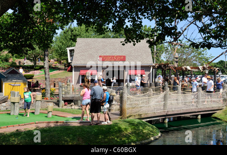 Tourists playing mini-golf on a sunny clear summer day at Pirates Cove in  Yarmouth, Cape Cod Massachusetts USA - Stock Photo