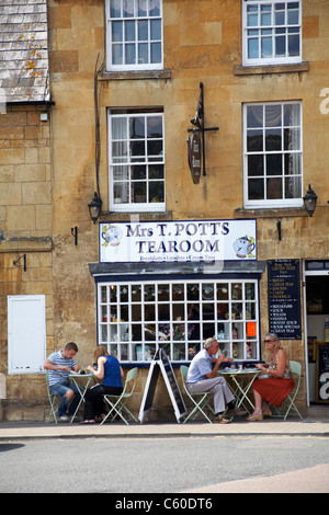 Enjoying food and drink at Mrs T. Potts tearoom in Moreton in Marsh in the Cotswolds in July - Stock Photo