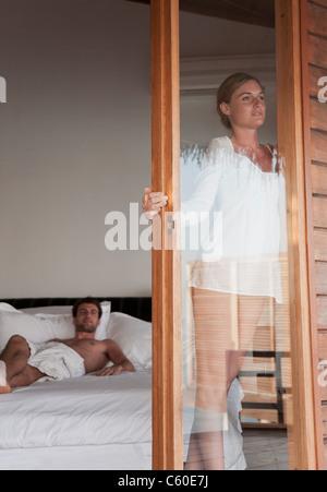 Woman standing in doorway of bedroom - Stock Photo