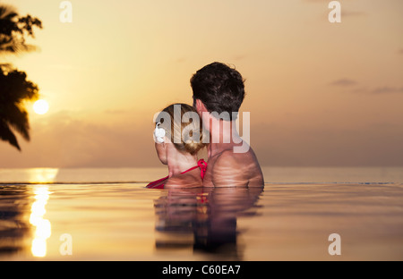 Couple embracing in infinity pool - Stock Photo