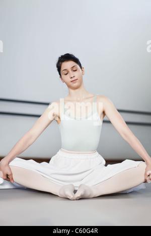 Ballet dancer stretching in studio - Stock Photo
