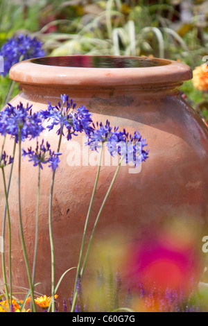 Large garden vase water feature in flowerbed, England, UK - Stock Photo