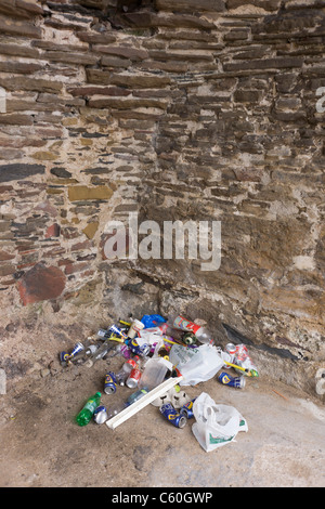 Beer cans and other rubbish collects in a corner of a heritage structure on the beach at Croyde, north Devon. - Stock Photo