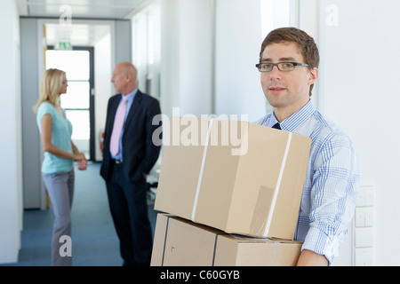 Businessman carrying cardboard boxes - Stock Photo