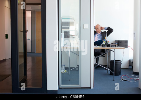 Businessman relaxing at desk in office - Stock Photo