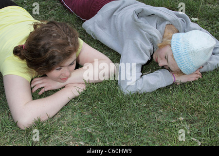 Two young girls laying in field of daffodils Stock Photo ...