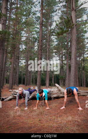 Runners doing push-ups in forest - Stock Photo