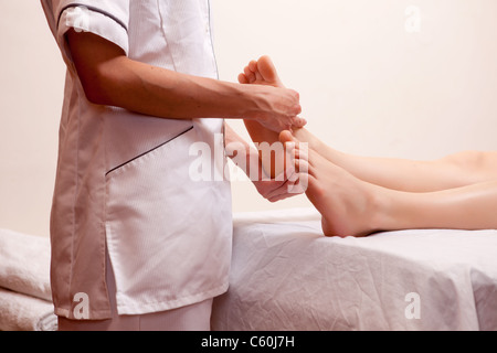 A professional masseur giving a foot massage in a spa - Stock Photo