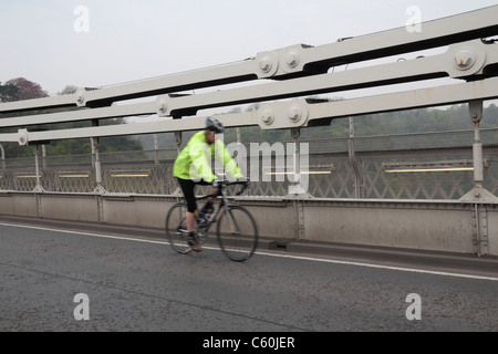 For scale, a cyclist crossing in front of the wrought iron chains on the Clifton Suspension Bridge, Bristol, England. - Stock Photo