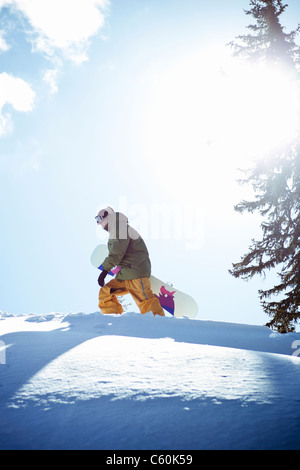 Man carrying snowboard on mountainside - Stock Photo